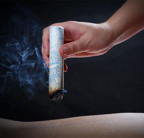 hand holding smoking moxibustion
